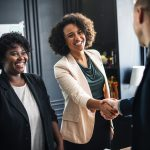 Women shaking hands, making a good first impression