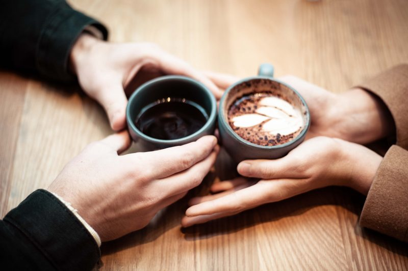 two sets of hands holding coffee on a micro-dating